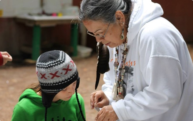A Native woman bends down to help a Native child with a craft project in an art classroom.