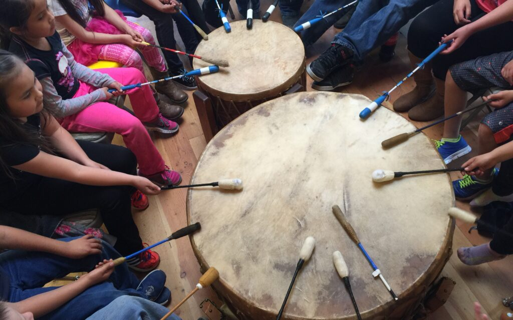 Native Blackfoot youth seated in a circle play a large drum.