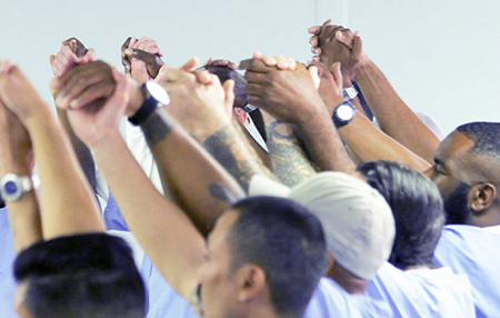 A group of incarcerated men wearing blue shirts raise their enjoined hands together above their heads.