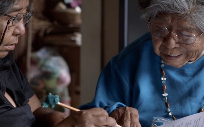 A Native American elder and her daughter sit at a table working on a dictionary to preserve their Wukchumni language.