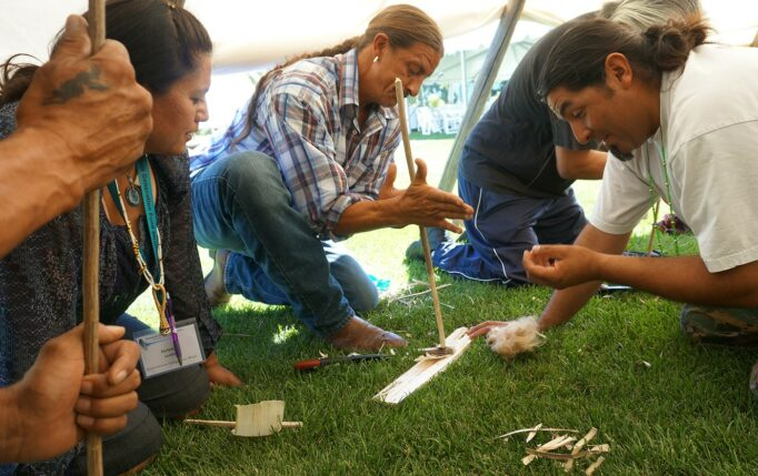 Indigenous people crouching in the grass practice fire-making with bow drills.
