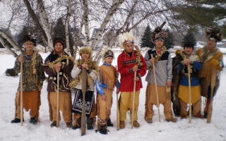 Students from the Akwesasne Freedom School stand in a line in the snow wearing traditional Mohawk dress.