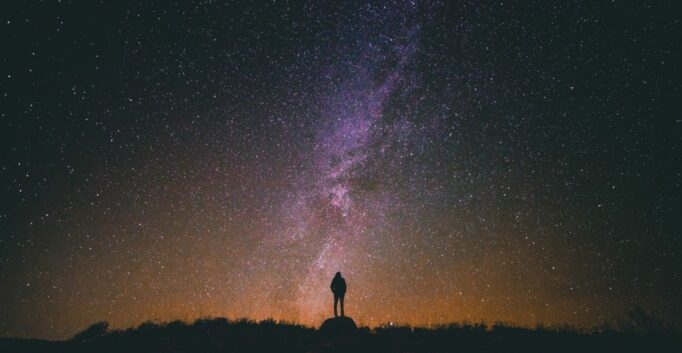 A figure stands silhouetted against a star-filled night sky.