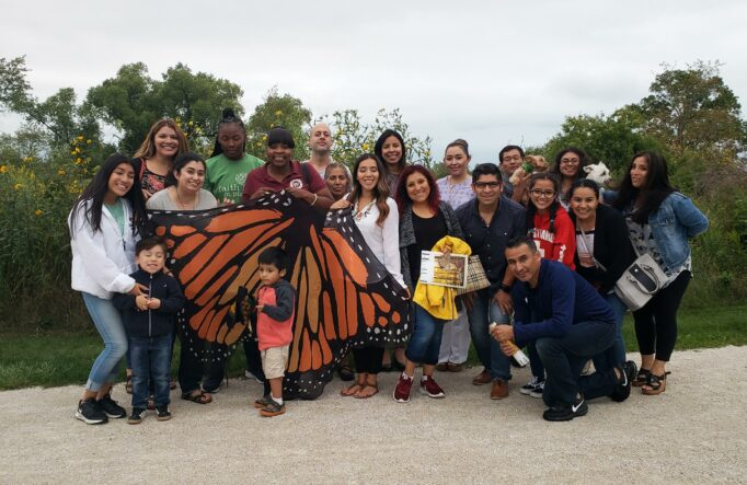 A crowd of approximately 20 people pose for a photo holding a banner that looks like monarch butterfly wings on a nature trail next to a prairie.
