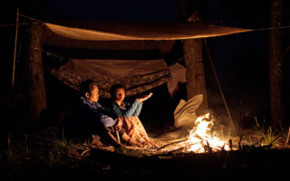 A man and woman sit by a fire under a shelter and talk.