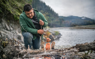 Sammy Gensaw (Yurok) of the youth group The Ancestral Guard prepares salmon in a traditional fashion on the Klamath River in the heart of the Yurok Reservation (northern California).