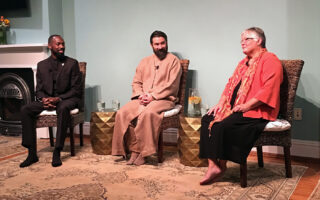 Spiritual leader Pir Zia Inayat-Khan sits with guest presenters at an event.