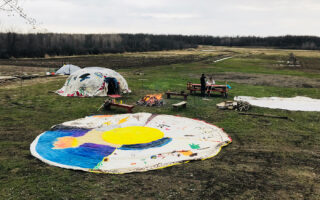 A painted tent canvas lies flat in the foreground and a sweat lodge stands nearby in a ceremonial area.