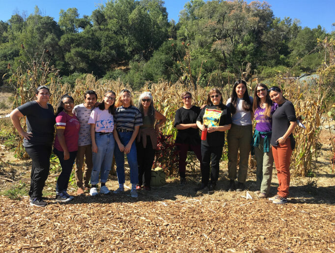 Native youth stand shoulder-to-shoulder in front of a small field of corn.