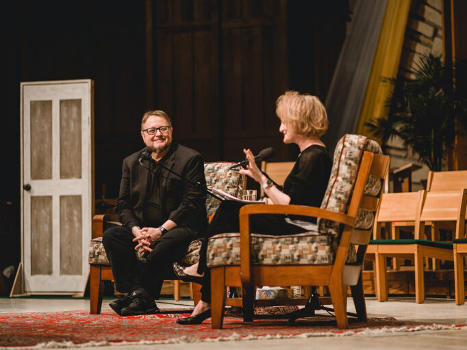 On Being host Krista Tippett interviews a man on stage at a live event.