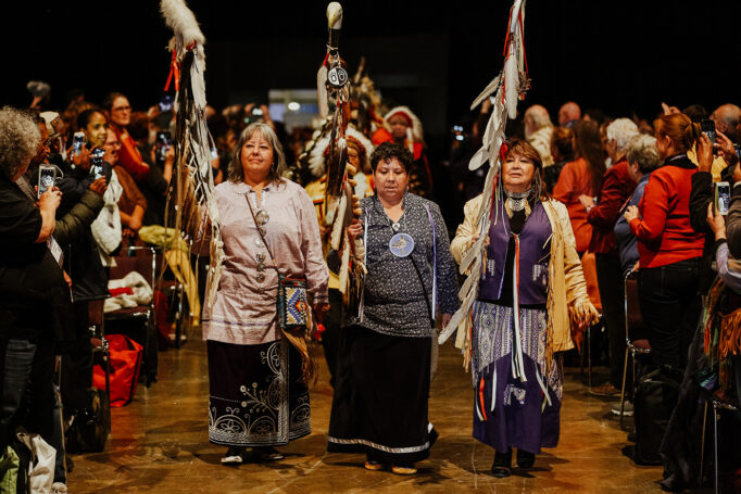 Indigenous representatives in ceremonial clothing walk through the hall of the conference in a procession.
