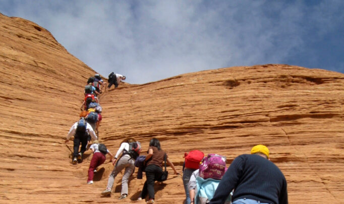 Young people and mentors hike in a line up a red rock hill in Arizona.