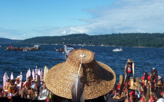 An Indigenous person wearing a cedar bark hat with a feather overlooks a group of participants in the Intertribal Canoe Journey.
