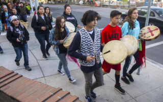 Native youth from the Salish School of Spokane march down a city street with ceremonial drums.