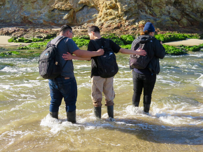 Three students help one another cross a river.