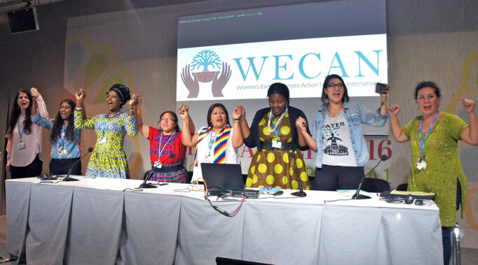 Women panelists stand raising their intertwined hands in front of a PowerPoint screen at a conference.