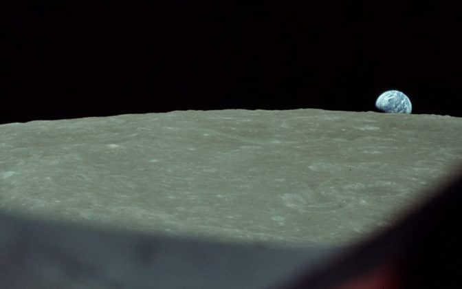 A photo of Earth rising over a moonscape.