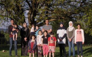 A Syrian refugee family poses for a photo in front of a tree in Canada.