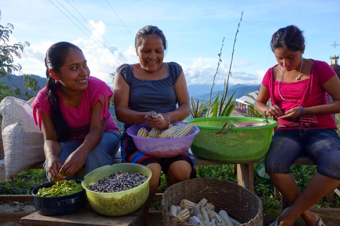 Three women sit together removing seeds from corn.