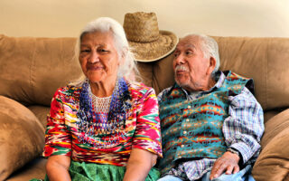 Two elderly people in traditional Zuni dress sit smiling on a couch.