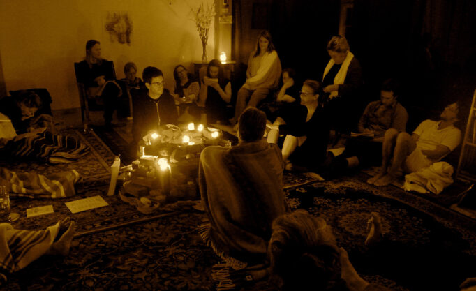 A roomful of people gather around candlelight.