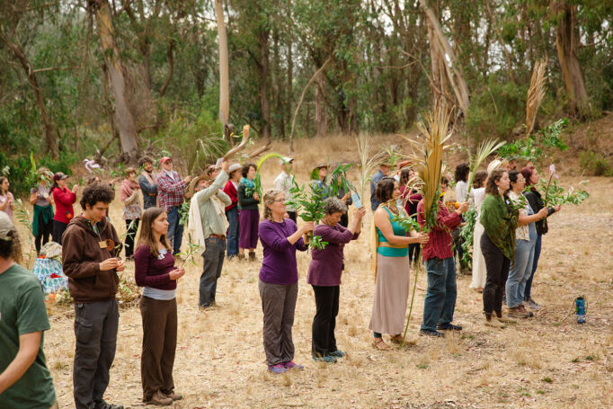 A group of people stand in a forest clearing, holding various offerings from nature.