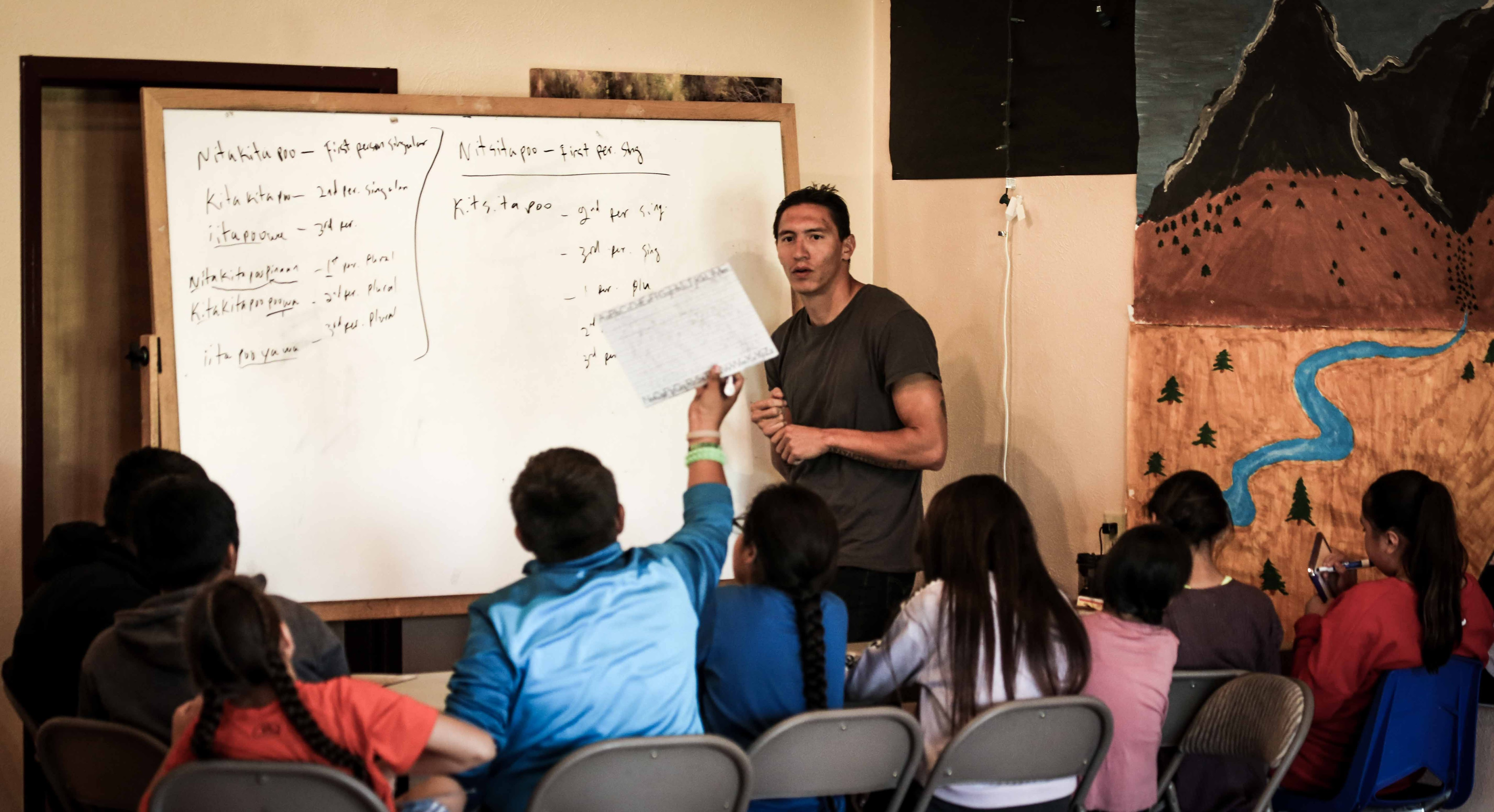 A Blackfoot teacher uses a whiteboard to teach young Blackfoot students at Cuts Wood School in Browning, Montana.