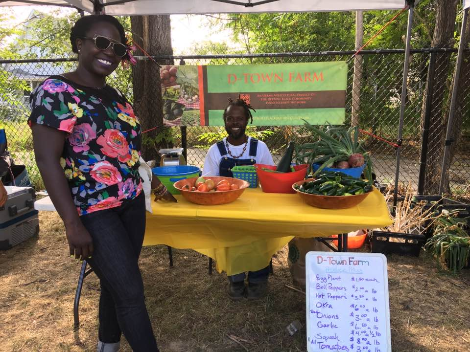Two members of the Detroit Black Community Food Security Network tend a table offering fruits and vegetables.