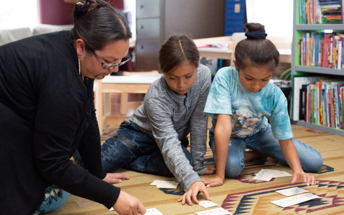 A Tolowa language teacher sits with two young students on the floor as they work together on a lesson.