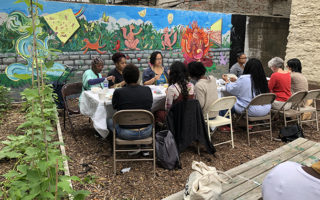 Participants at Kelly Street Garden sit around a table in the garden near a mural.
