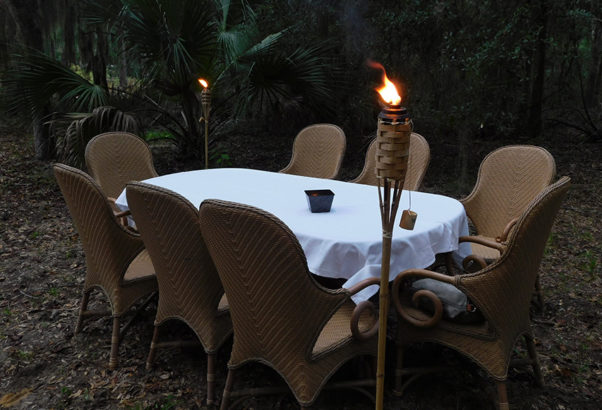 An outdoor table by candlelight awaiting participants of Kitchen Table Talk.