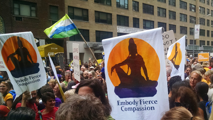 Participants in climate change march carry signs with Buddhist message.