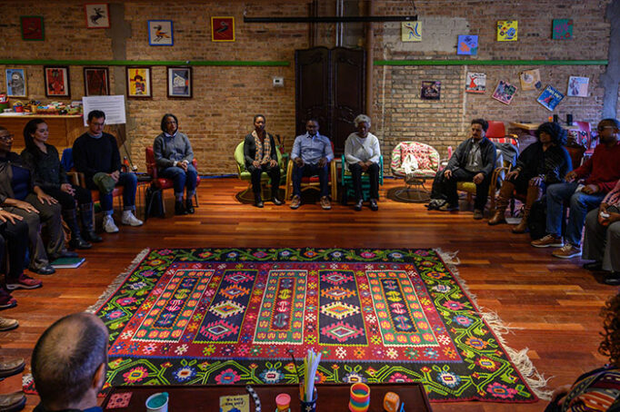 Spiritual Ecology and Culture participants sit in a large circle in a colorful room.