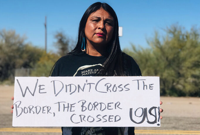 "A woman holds a sign that reads ""We didn't cross the border. The border crossed us."""