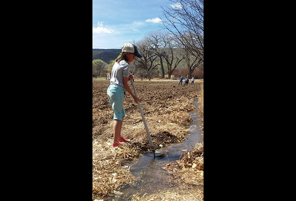 A girl works the acequia with a tool.