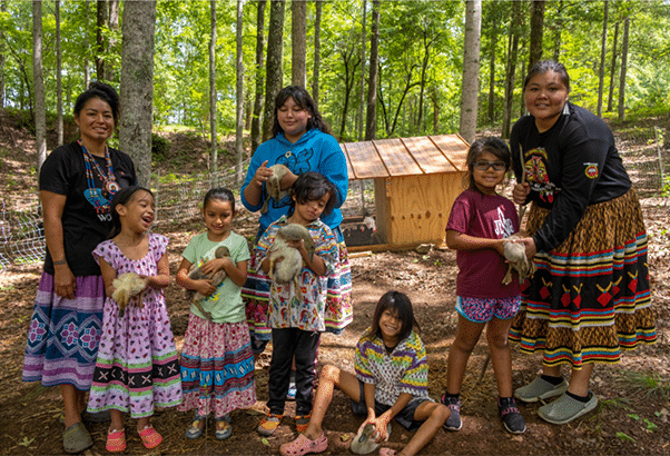 Young members of the Ekvn-Yefolecv eco-village under a forest canopy with ducklings.