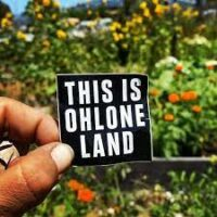 """A person holds a sign that says """"This Is Ohlone Land."""""""