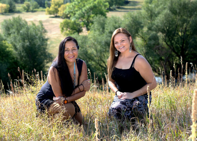 Dr. Ruby Gibson and Kara Big Crow of Freedom Lodge, sitting in a field in the rolling hills.