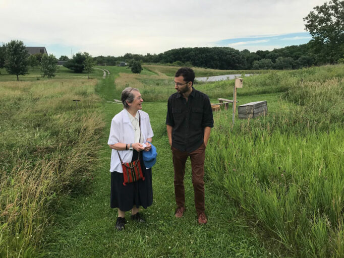 Two people standing in a green field.